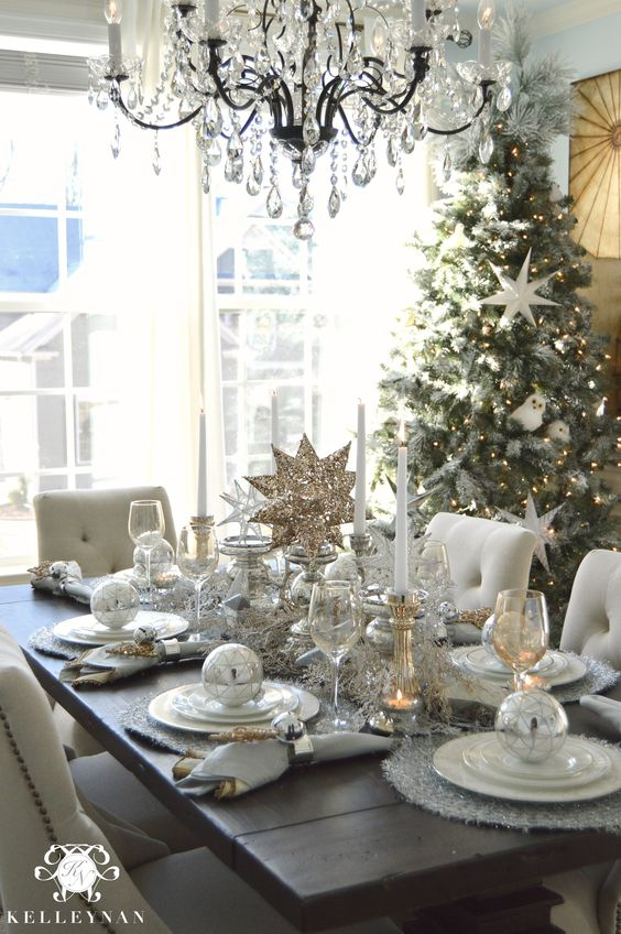 Christmas table idea with neutral, silver, and gold decor and stars for tablescape and place settings. Flocked nature tree in the dining room with crystal chandelier: