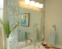 tile accent wall behind mirror, add glass cove molding tiles to frame mirror