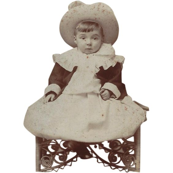 This cabinet photograph measures 4 1/8 x 5 3/4.  The image is a small child with a large hat, ruffled color, dress, and dark jacket.  The curly wicker