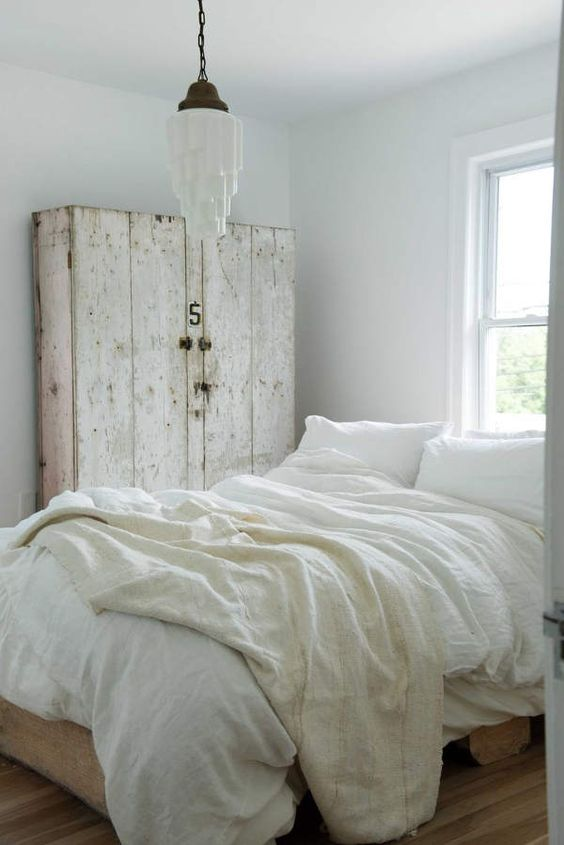 An all white bedroom with #whitelinen bedding, a rustic white country cabinet, and a vintage light in a cool chic #bedroomdesign by #LeanneFord.