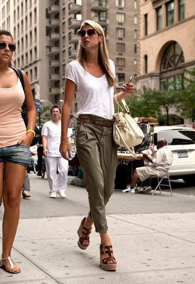Shop this look on Lookastic: https://lookastic.com/women/looks/v-neck-t-shirt-chinos-wedge-sandals/19178   — White V-neck T-shirt  — Beige Leather Tote Bag  — Dark Brown Leather Belt  — Olive Chinos  — Dark Brown Leather Wedge Sandals