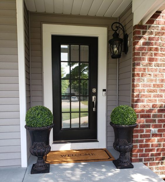 Black front door with topiary urns