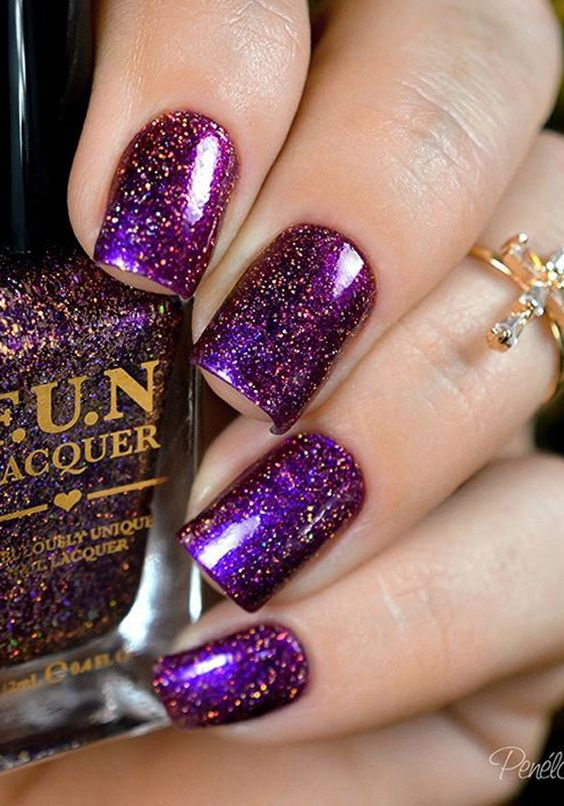 Galaxy inspired Purple nail art design. The glitter polish consists of gold and purple glitters making the nail art design resemble the galaxy.…