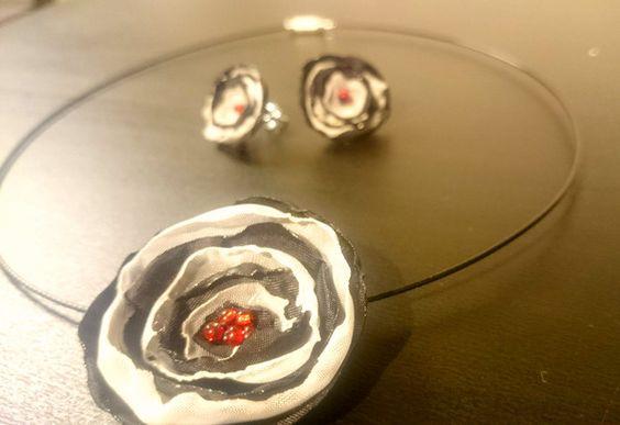 Modisches Schmuckset mit schwarz/weißen Blüten aus Satin, verziert mit schimmernden roten Perlen. Das Set besteht aus einem Paar Ohrstecker und einem Collier mit passendem Anhänger, beides lässt...