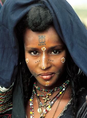 Africa | Portrait of a Wodaabe woman in Niger.  Her face combines both permanent tattoos and face painting elements