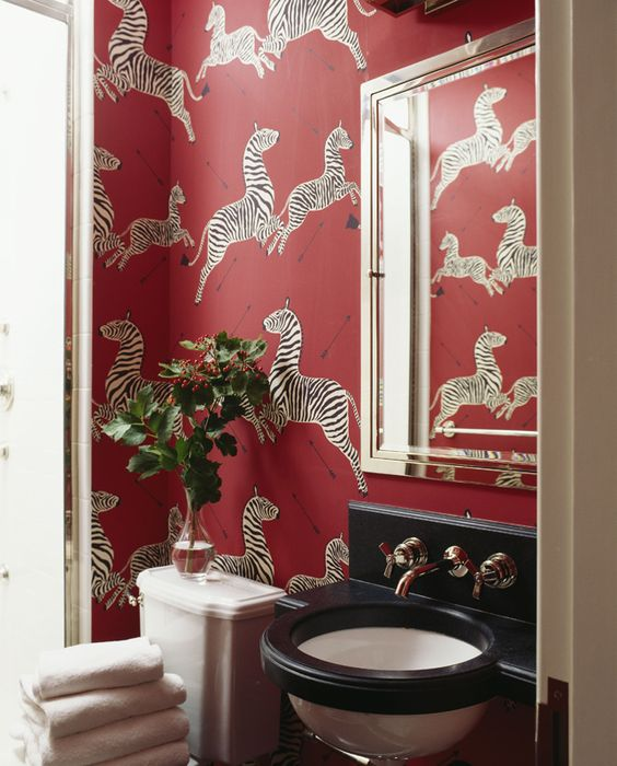 This red and black bathroom with Scalmandre wallpaper is elegant yet whimsical