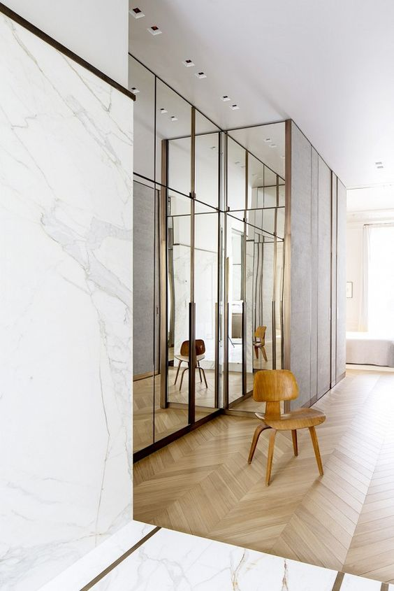 large closet area with mirrors on door, wooden chair, marble walls