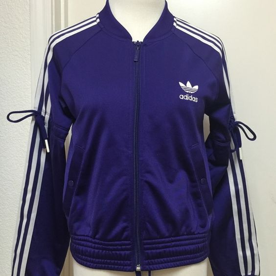 Adidas Originals Track Jacket Ladies Medium Purple Adidas Ladies track jacket with front zipper. Color is a deep purple with light silver/white stripes. The sleeves have shoe string ties at the elbow area and also shoe string inside the jacket adds extra style :) Tags say medium but runs a little smaller. Armpit to armpit 34 inches. Elastic waistband at the bottom of jacket 32 inches. Condition is 8/10. No stains. Adidas Jackets & Coats
