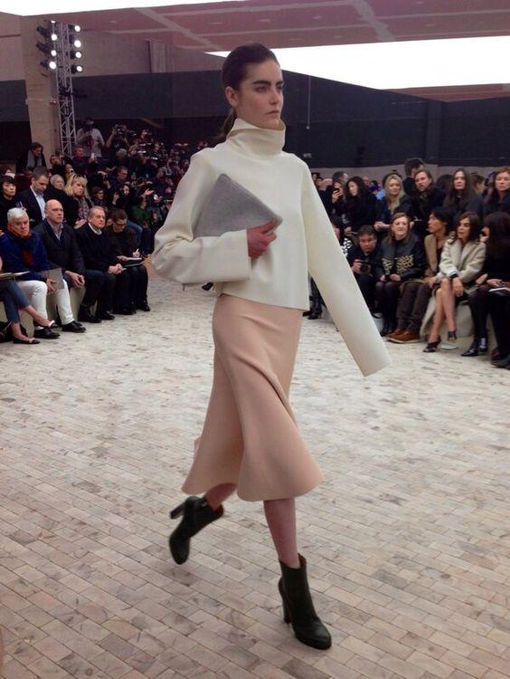 Col roulé écru, jupe rose pâle, pochette grise et boots noires au défilé #Celine