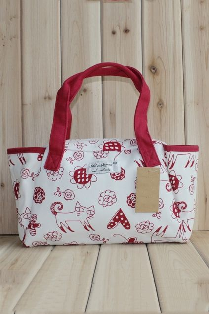 This handbag crafted in canvas, featuring cat and flower print to the main, double handle, top zip closure, pockets to the interior.$30