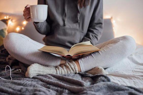 mulher sentada na cama lendo livro com caneca na mão hygge