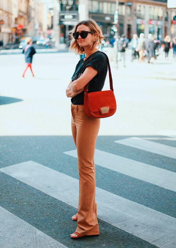 Street style Adenorah com look calça marrom, tshirt e bolsa laranja