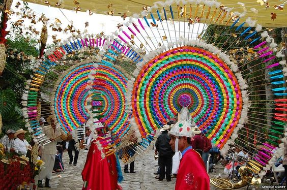 """""""Nahuatl dancers wearing penachos celebrate their heritage in the streets at the Feria del Huipil in Mexico."""""""