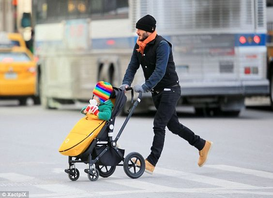 Snug: David wrapped up the youngest member of the Beckham clan in a green padded coat and ...