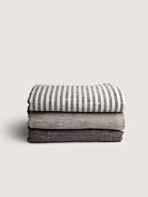 """DESCRIPTIONA thick luxurious linen blanket with classic colored warp and  white weft. It will keep you at a comfortable neutral temperature in warmer  months and perfect layered in the fall. Also makes for an ideal sofa throw.  Made of 100% linen.  DIMENSIONSApprox. 83""""l x 57""""w DETAILSMade in Lithuania by Fog Linen Work"""
