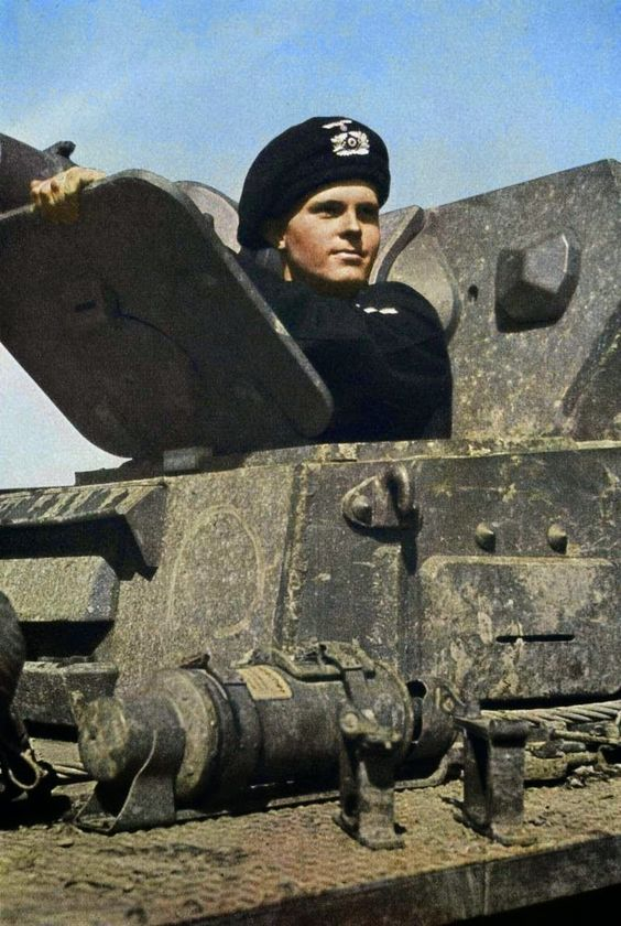 """Early war photo of German Panzerkampfwagen IV Ausf.C or D (Sd.Kfz. 161) driver wearing the beret-type """"Schutzmütze"""" (protective cap). This headgear consisted of the soft padded crash helmet, which served to protect the heads of the panzer crew from injuries sustained when the vehicle was motoring over rough terrain, and the black cover. The helmet was circular in shape and manufactured with 1.5cm thick felt or red rubber sponge. The exterior was covered in black cloth and the interior was…"""