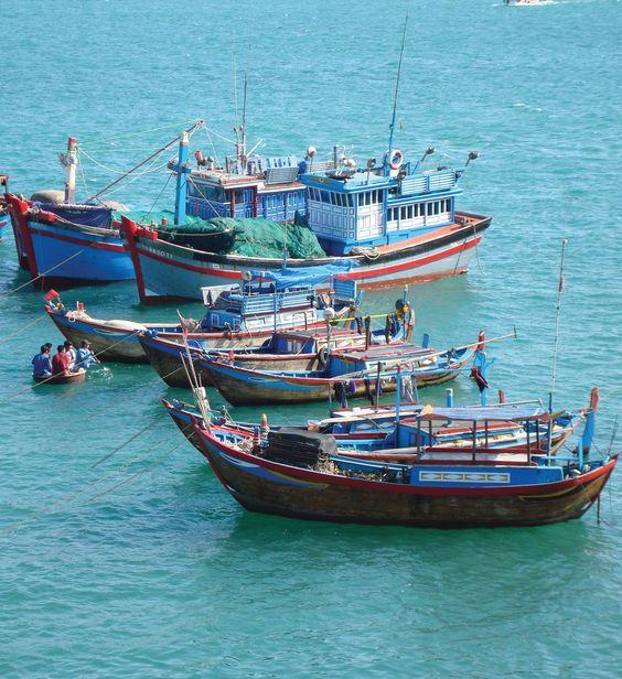 Fishing boats float off the coast of Vietnam.: