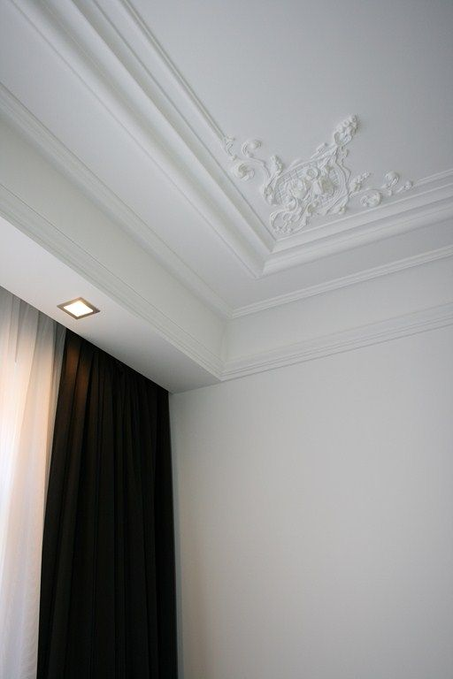 White interior with classic moldings combined with recessed lighting _