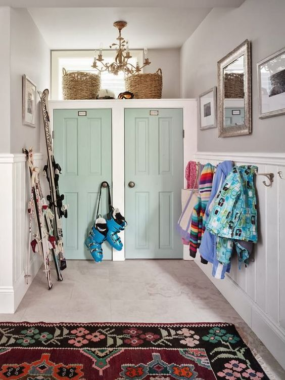 Twin vintage doors pained aqua green in farmhouse #mudroom with ski equipment by #SarahRichardson