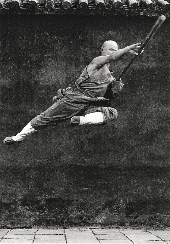 """SHAOLIN: """"Bow and Arrow.Crouching Cat."""" On and on the instructor calls the stances. """"Three Pillars. Seven Stars."""" There's a lot of counting. We bend our legs and count. We stretch back and count. We count the minutes till its over. - Samurai Kids 3:Shaolin Tiger"""