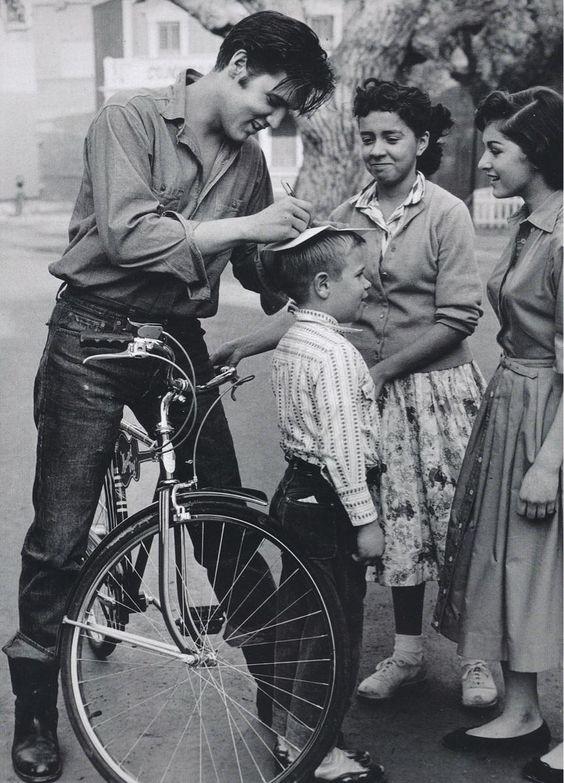 Elvis signing autographs on a boys head, 1959.