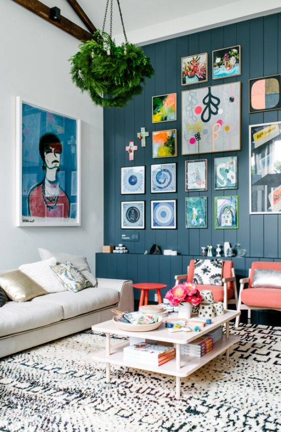 Living room, colorful art pieces, blue wall, table, white couch, golden pillows, pink chairs