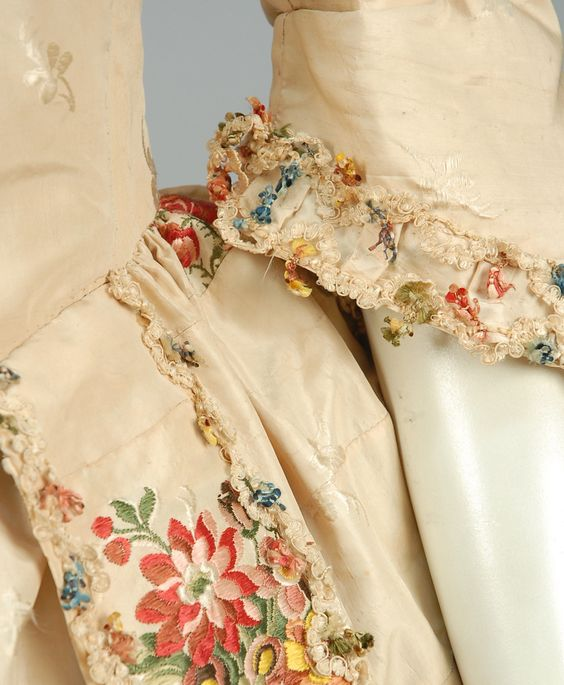 Detail sleeve, open robe, Canada, 1750-1775. Ivory silk brocaded with small tone on tone flowers and larger polychrome floral clusters, semi boned bodice with square-cut neckline and elbow length sleeve, pleated cuff decorated with fancy cord and polychrome tassels, trained open skirt with cord-trimmed furbelows, matching petticoat, bodice lined in cotton and linen.