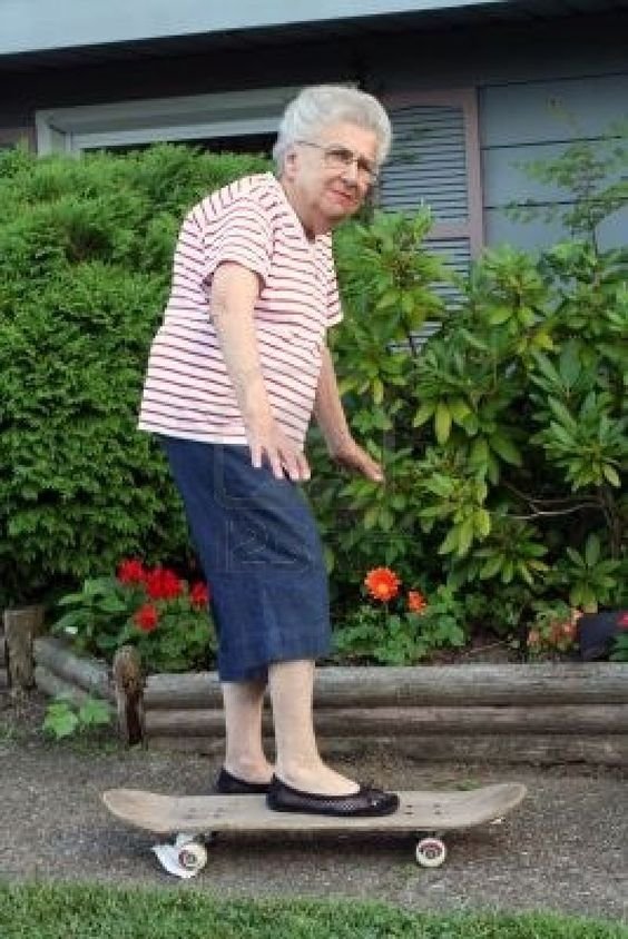 Senior citizen woman on a skateboard. Stock Photo