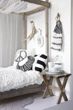 Slaapkamer met hemelbed in zwart/wit/naturel.