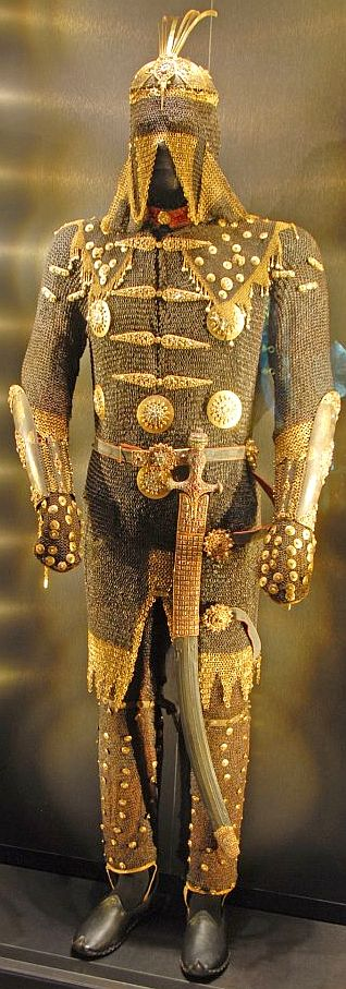 Ottoman Empire armor belonging to Sultan Mustafa III consisting of migfer (helmet), zirah (mail shirt), mail trousers, kolluk/bazu band (vambrace/arm guards), shamshir (sabre), decorated with gold and encrusted with jewels, 18th century, exhibited in the Imperial Treasury of Topkapi Palace, Istanbul, Turkey...