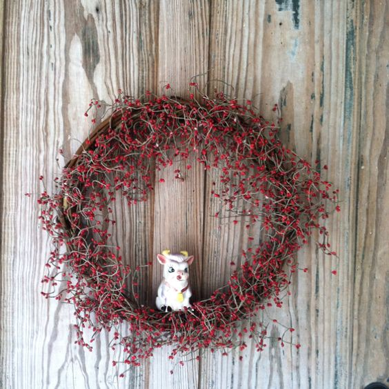 Old door with cute little cow in a wreath