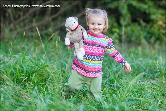 cute blonde girl in field walking with sock monkey photo