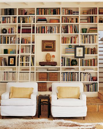Home library. Near Santa Barbara, CA. The living room is filled with bright light; white walls and furnishings reflect the sunshine still more. The floor-to-ceiling bookcases are original to the house; woven baskets hold family photos. Wide thrift-store chairs are slipcovered in sturdy cotton. A cowhide rug tops a sea-grass carpet; behind those are vintage terra-cotta tiles.