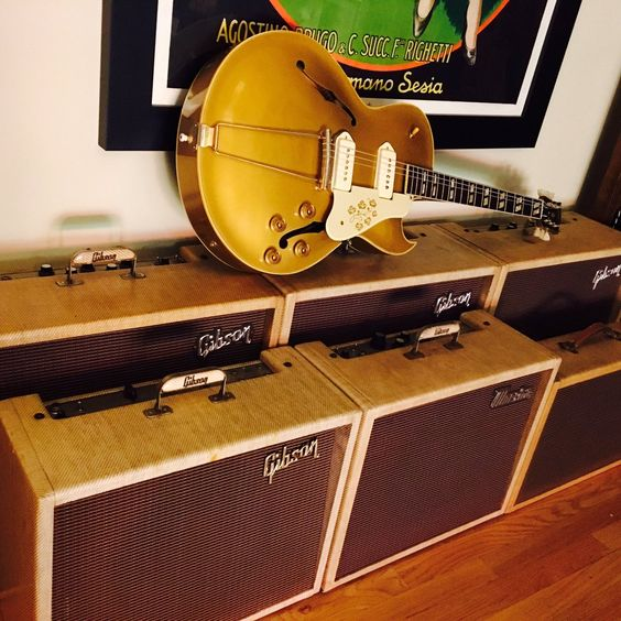 A nice farm fresh 54 Gibson ES-295 on top of a pile of old fashioned Gibson amps.