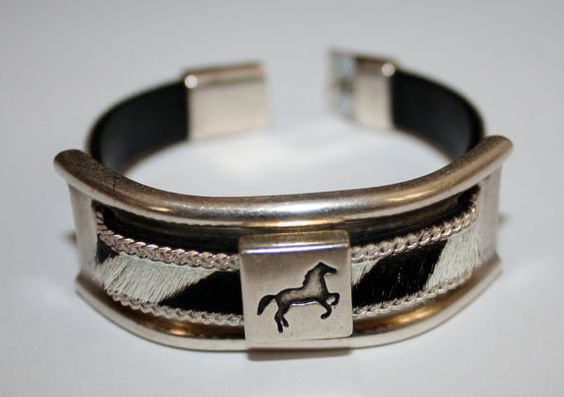 Horse slider on colt hair flat leather cord slips into the sides of an antiqued silver large bracelet bar as a bold center focal. Bracelet