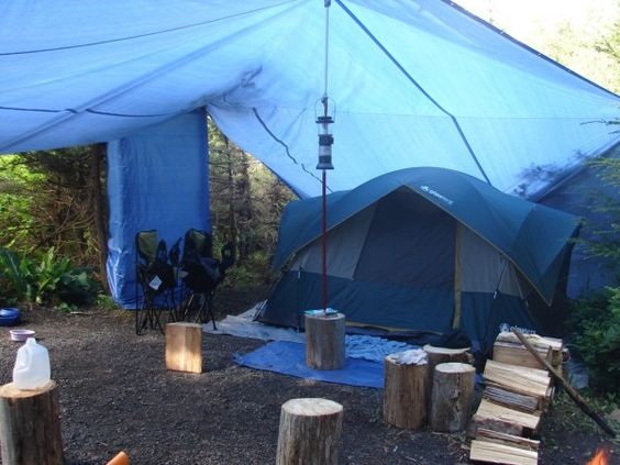 One of our actual campsites for a 5 day trip. The tarp wrapped around the trees behind the chairs is a shower stall. (07/12)