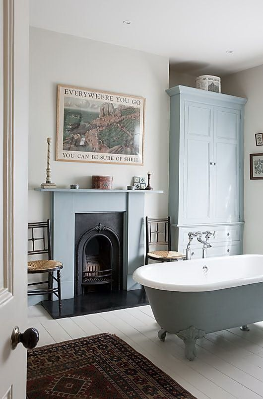 fireplace in the bath, armoire, and clawfoot tub
