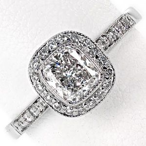 Modern diamond engagement ring sparkles with a micro pave band and halo. The halo holds a bezel set cushion cut diamond, and the band tapers in as it reaches the halo. Cushion Enchantment by Knox Jewelers