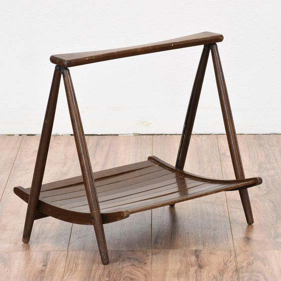 This mid century modern magazine rack is featured in a solid wood with a dark walnut finish and tapered legs. This magazine holder is in great condition with a curved panel base and sleek modern design. Unique side table perfect for books!   #midcenturymodern #storage #magazinerack #sandiegovintage #vintagefurniture
