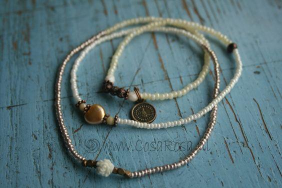 Armband met kleine kraaltjes geregen op elastiek, met roosje, hartje bedeltje en koperen onderdelen