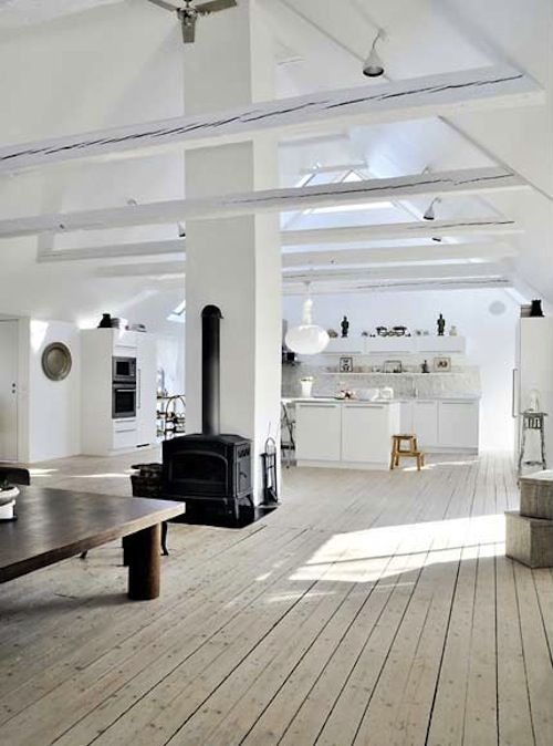 big open space in whites. high ceilings, whites, heat stove.