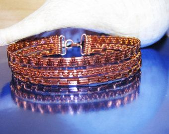 Copper and Sterling Silver Wire Woven Bracelet This stunning little beauty has a center focal of Sterling Silver and Copper beads. The sides are accented with three arrows on each side. Our Signature Closure secures it.  As with all of our copper creations, it is polished, double sealed and cured to prevent tarnish. We want our creations to look beautiful each and every time you put it on.  We love what we do and it shows in our quality. Let us design something beautiful for you today.