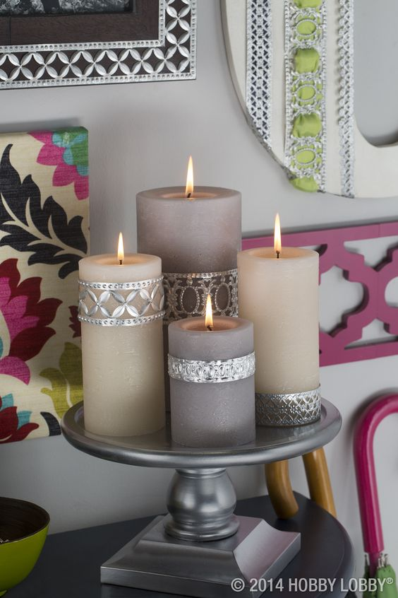 Glam up your candles with this easy DIY! Wrap standard-issue pillars with metal  ribbon—use nails or pushpins to secure— and fan the flames of gorgeousness.