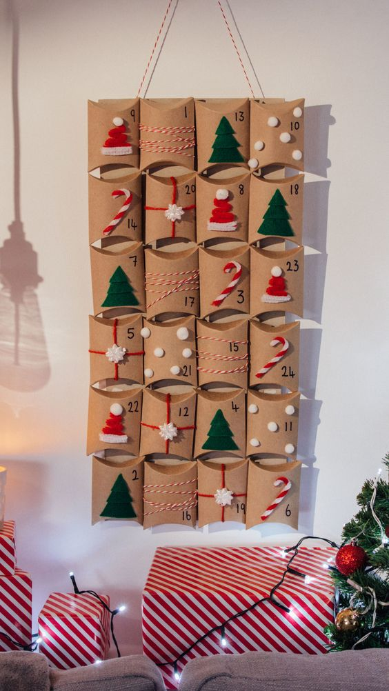 Recipe with video instructions: Count down to the Big Day with this home-made advent calendar Ingredients: cereal box, 24 pillow boxes, velcro, red, white and red & white pipe cleaners, small white pom poms, green felt, string, bows, glue gun, scissors, black felt pen, white chocolate, melted, Christmas sprinkles, silicone heart ice cube tray, tin foil