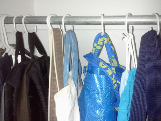 Hang your bags with shower curtain hooks. The hooks take up less space than hangers. And it's a great way to compartmentalize the things in your closet that don't have a place — scarves, belts, socks.