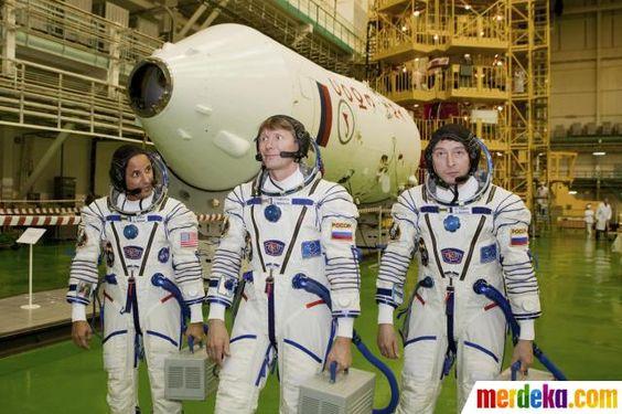 Awak International Space Station (ISS) astronot dari AS Joseph Acaba (kiri) dan kosmonot Rusia Gennady Padalka (tengah) dan Sergei Revin berpose di dekat pesawat ruang angkasa Soyuz di kosmodrom Baikonur.