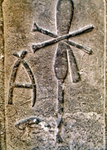 Stele della regina Merit-Neith, Museo del Louvre. Il simbolo della dea: le due frecce incrociate sopra lo scudo