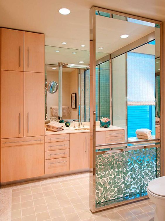 For upscale functionality in this midcentury modern master bathroom designer Mary Anne Smiley added a resin privacy panel with a chrome frame, grab bar and aqua selenite ornamentation.