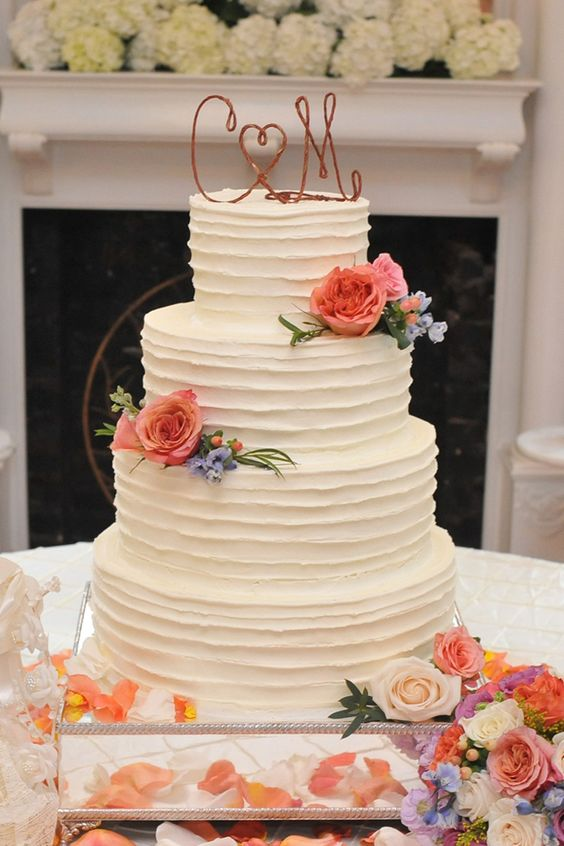 A beautiful brushed buttercream wedding cake from Magic Muffins. Flowers by CD Florals. The Sonnet House weddings. Photo by Robert Norris Photography