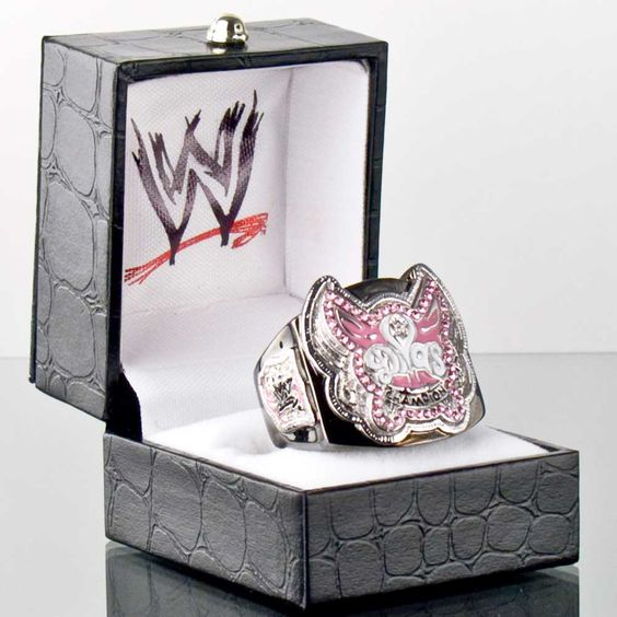 Introducing the Officially Licensed WWE Divas Championship Belt Replica Finger Ring. Made by Figures Toy Company. The ring is made of brass to simulate the gold and also is finished with black hematite to simulate the belt strap. The ring has an adjustable shank that fits rings size 6 to 12 with ease. Ring will be shipped in a black jewelry box with the WWE logo printed on the inside of the box